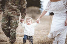 Soldier Father With His Wife Holding The Hands Of Their Son From Both Sides And Walking In A Field