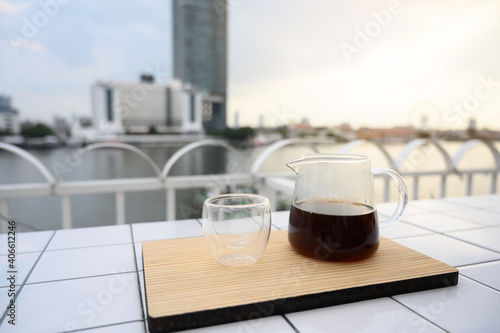 Foto Drip freshly brewed coffee in glass jar with a cup on wooden tray
