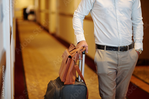 Fototapeta Cropped image of man with suitcase and leather bag walking in hotel corridor to