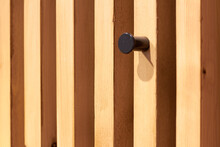 A Nail Hook Designed For Clothing Is Screwed Into A Wooden Bar