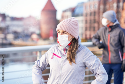 Obraz Adult couple jogging in the city in masks during lockdown - fototapety do salonu