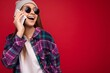 Leinwandbild Motiv Closeup photo of beautiful happy positive young blonde female person wearing hipster purple shirt and casual white t-shirt grey hat and sunglasses isolated over red background holding in hand and