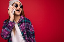 Closeup Photo Of Beautiful Happy Positive Young Blonde Female Person Wearing Hipster Purple Shirt And Casual White T-shirt Grey Hat And Sunglasses Isolated Over Red Background Holding In Hand And