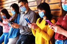 A Group Of Millennials During The Covid-19 Pandemic Stands Against A Wall And Uses A Telephone - A Group Of Masked Friends Hold Phones In Their Hands - Mobile Phones And Social Networking Concept