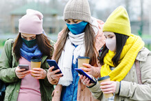 Three Girls During The Coronavirus Walk On The Street And Look At A Mobile Phone - Millennials In Smartphones Use Social Networks For Entertainment - Young Girls Wearing Masks On Their Faces Protectio