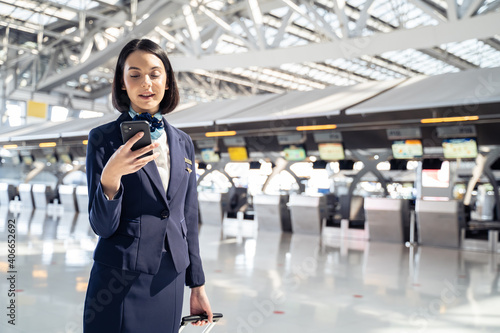 Tablou Canvas Caucasian beautiful flight attendant using mobile phone in the airport
