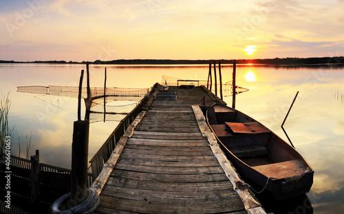 Obraz na plátně Steg mit Ruderboot im Sonnenuntergang
