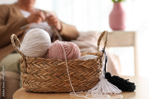 Basket with yarn and elderly woman knitting on background. Creative hobby