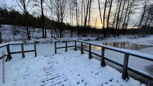 zimowy krajobraz częściowo zamarzniętej rzeki koło Włodawy dużo śniegu niebieskie niebo złota godzina  - fototapety na wymiar