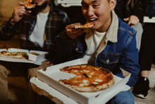 Young Adult Friends Eating Pizza At Night Outside On The Street After Nightout