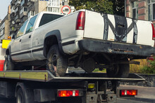 Old Wrecked Broken Pickup Vehicle Accident Transportation On Flatbed Tow Truck Machine On City Street. Emergency Road Assistance Service On Motorway. Automotive Trailer Carrier Transport