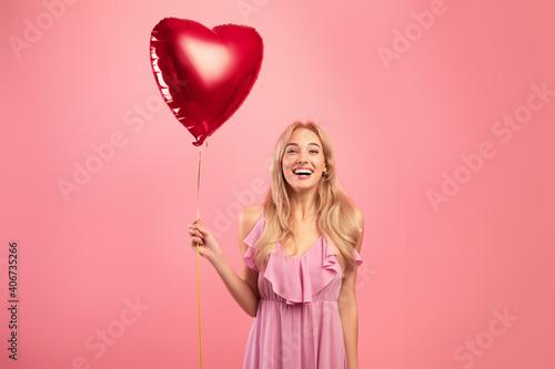 Obraz na płótnie Portrait of joyful blonde woman in dress holding red heart shaped balloon for Va