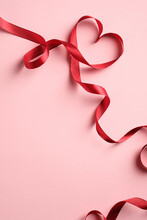 Red Heart Shaped Ribbon On Pink Background. Happy Valentine's Day Or Mother's Day Concept.