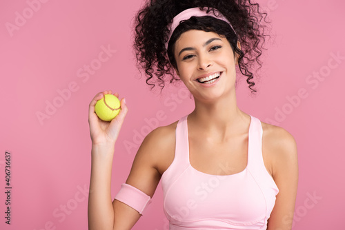 Valokuvatapetti cheerful young woman holding tennis ball isolated on pink