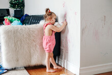 Funny Cute Baby Girl Drawing With Marker On Wall At Home. Toddler Girl Child With Milk Bottle Playing At Home. Authentic Candid Childhood Lifestyle Moment. Young Artist Painting On Wall At Living Room