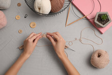 Woman Knitting With Threads At Grey Table, Top View. Engaging Hobby