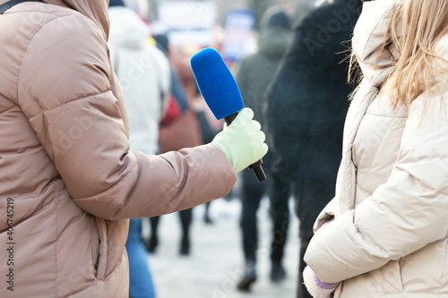 Media interview during winter at street, journalist holding microphone interviewing unrecognizable female person