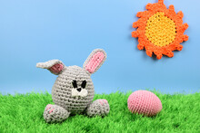 Knitted Easter Bunny Next To A Pink Egg Depicted On Green Grass