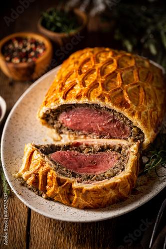 Perfect homemade juicy Beef Wellington, tenderloin dish on rustic wooden table © petrrgoskov