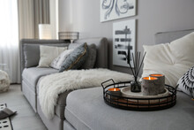 Candles And Aroma Reed Diffuser On Grey Sofa, Space For Text