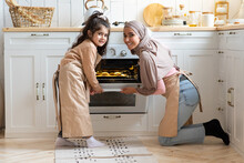 Portrait Of Happy Muslim Family Mother And Daughter Baking Together In Kitchen