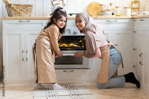 Portrait Of Happy Muslim Family Mother And Daughter Baking Together In Kitchen Fototapete