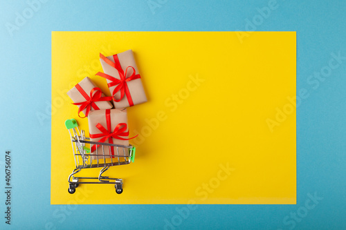 Obraz na plátne Gift box with red ribbon in mini grocery cart on pink background