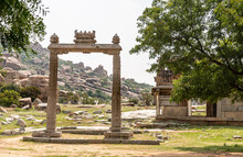 Hampi, Karnataka, India - November 5, 2013: Ruin Of Ancient Temple. Closeup Of Beige Stone Sculpted Free-standing Portal With Green Hill Full Of Brown Stone Boulders Under Silver Sky. Green Foliage Ar