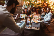 Young Adult Taking Photo Of His Friends With Phone At Dinner Party