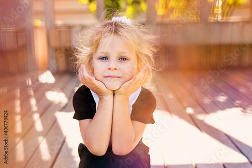 Billede på lærred cute little blonde girl sitting on the fresh glass. top view