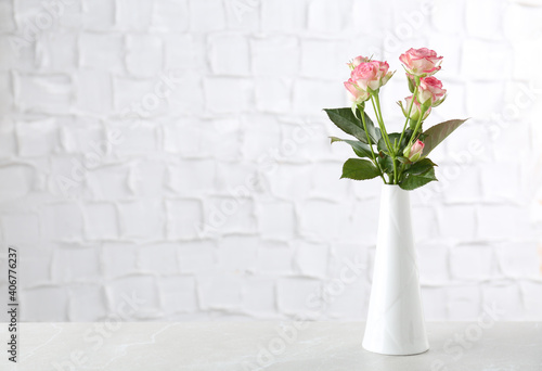Vase with beautiful pink roses on white table near brick wall