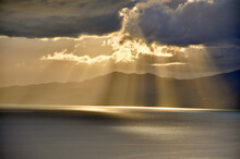 The Sun Behind The Clouds With Rays Of Light Shining Down On Sea. Rays Of Sun Peeking Through Clouds Onto The Adriatic Sea Defrost Rijeka City, Croatia.