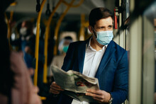 Male Entrepreneur Reading Newspaper And Wearing Face Mask While Commuting By Bus.