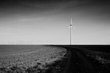 A Lone Windmill In The Foreground With A Line Of Windmills Off In The Distance In This Black And White Image.  An Otherwise Empty Landscape.