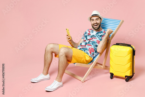 Fototapeta Full length happy young traveler tourist man in hat sit on deck chair using mobile cell phone doing winner gesture isolated on pink background. Passenger travel on weekend. Air flight journey concept. obraz na płótnie