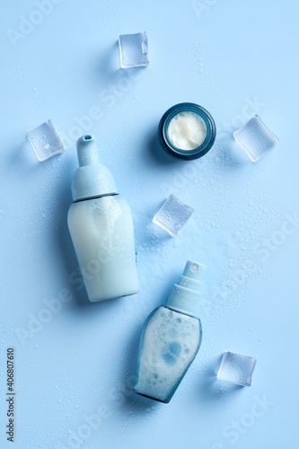 Moisturizing cosmetics and ice cubes on a blue background. Top view.