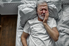 Sad Lonely Senior Lying On Bed In A Hospital, Hospitalization Concept. Suffering From Disease, Teeth Ache, Crying From Pain