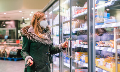 Fototapeta Boks Woman at supermarket freezer section wearing face mask