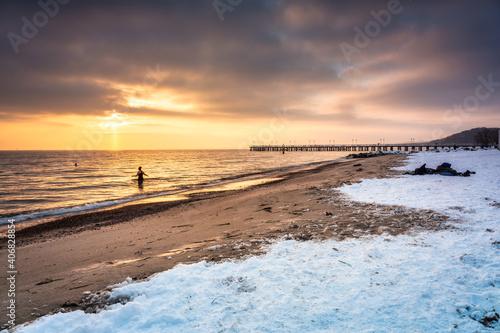 Obraz Amazing snowy beach in Gdynia Orlowo at sunrise, Baltic Sea. Poland - fototapety do salonu
