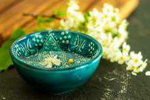A Blue Oriental Turkish Bowl With Transparent Water On A Background Of White Cherry Flowers On A Wooden Board And A Black Background. Copy Space. Spring Holiday Concept.
