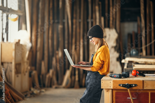 young female carpenter looks drawings on a laptop during a break in work in workshop