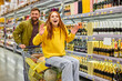 family have fun in the aisle of grocery store, woman sits on cart and enjoy shopping with husband