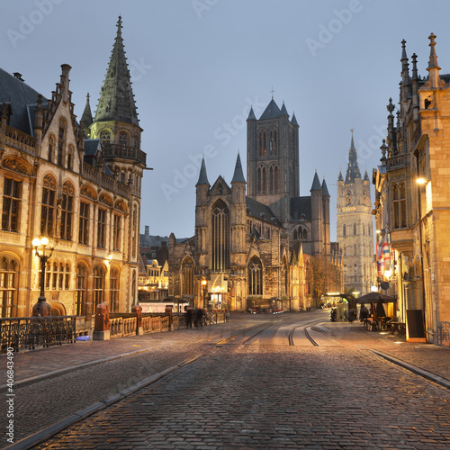 Obraz Illuminated street near St Michael bridge and St Bavo's Cathedral in a historical center of Ghent city. Night cityscape. Travel guide, national landmark, sightseeing theme. Belgium - fototapety do salonu