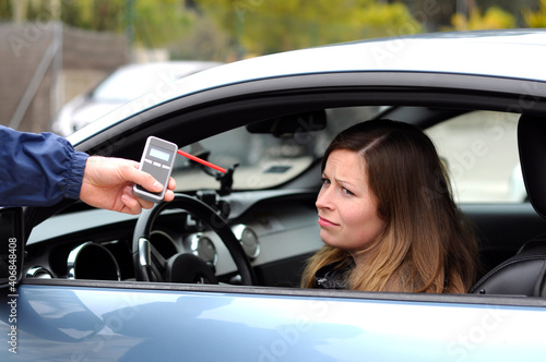 Tableau sur Toile drink and drive crashed young female driver being subject to test for alcohol content with use of breathalyzer