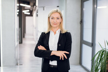 Indoor Office Portrait Of Pretty Mature Blond Business Lady, Wearing White Shirt And Black Jacket, Standing With Arms Crossed In Modern Office Interior. Businesswoman In Office Corridor
