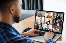 Over Shoulder View To A Laptop Screen With Many Multiracial Successful Employees, Coworkers Communicating By Video Call, Online Meeting Concept. Video Conference With Many People Together