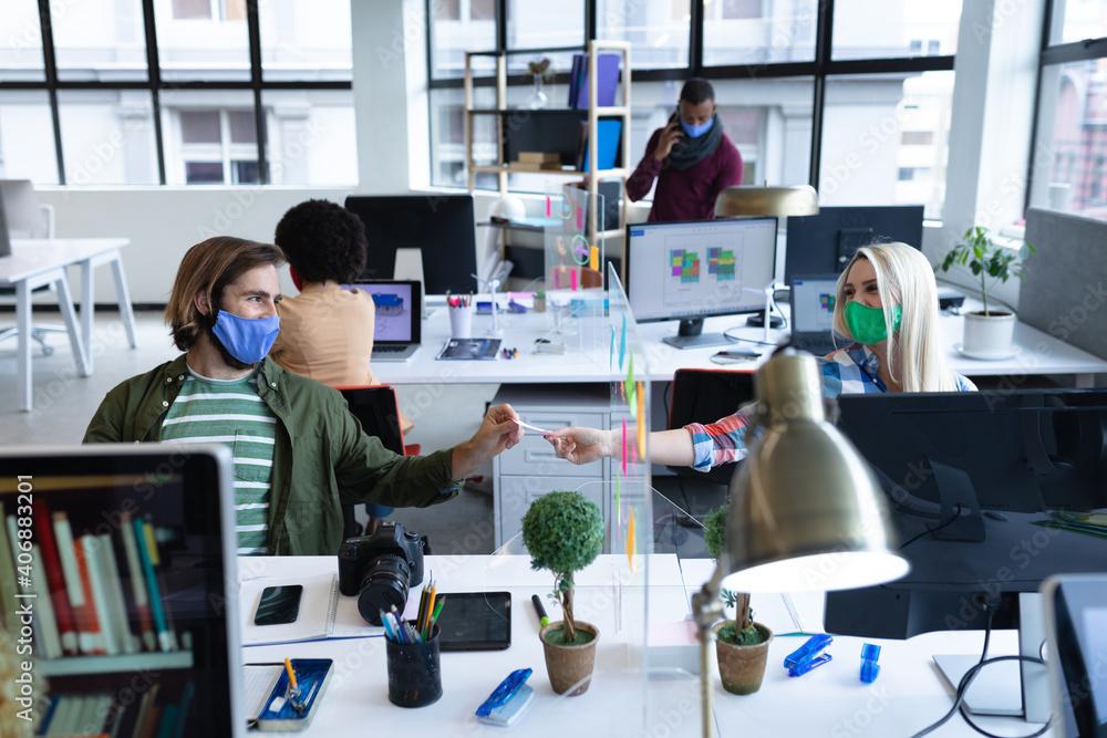 Fototapeta Caucasian business people wearing face masks in creative office - obraz na płótnie