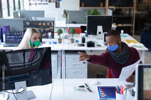 Fototapeta Two diverse business people wearing face masks in creative office obraz na płótnie