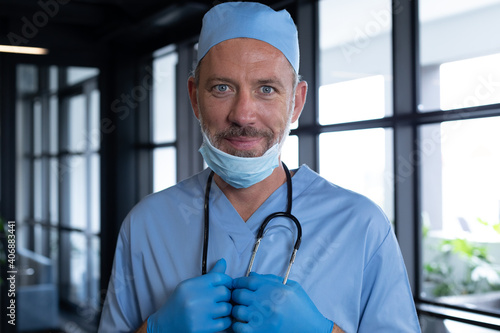 Portrait of caucasian male doctor standing looking at the camera and smiling
