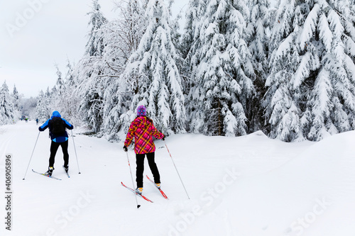 Group of people cross country skiing on beautiful winter day. Cross-Country Skiing in Germany, in snowy forest.